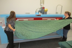 Staff processing table cloths through the ironer